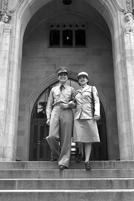 A male and a female student in World War 2 uniform walk down the Indiana Memorial Union stairs
