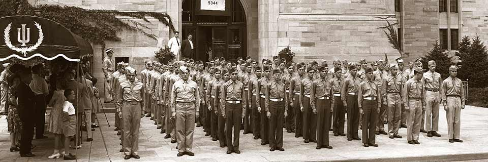 U.S. military members stand at attention on the IU campus.